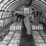 The crew of a Douglas C-47 Skytrain load up a cargo of milk in Frankfurt Rhine-Main, part of the Berlin airlift during the Berlin Blockade, August 1948. The Soviet Union had blocked Allied access to West Berlin by land. (Photo by Henry Grant Compton/FPG/Getty Images)
